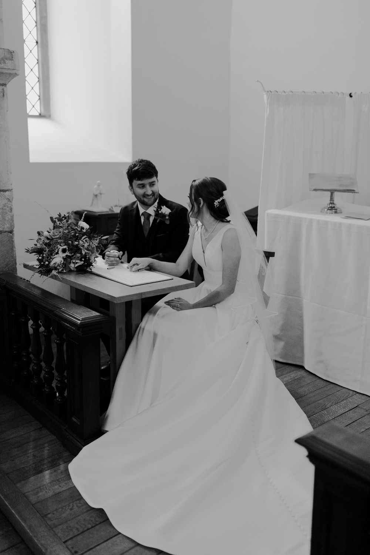 farnham castle wedding chapel ceremony bride and groom signing the register