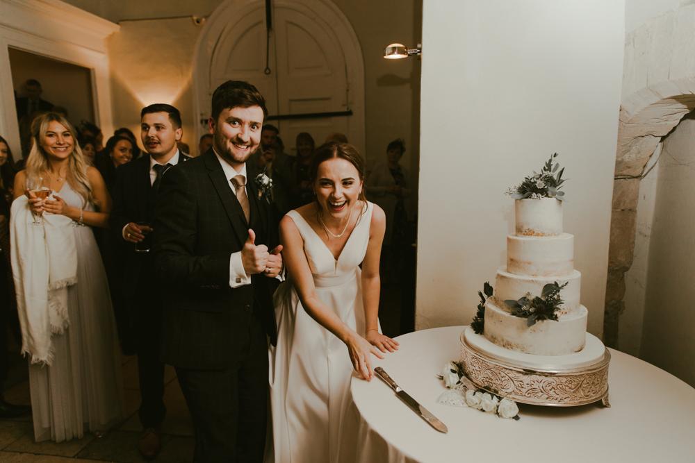 cutting the cake wedding farnham castle bride and groom