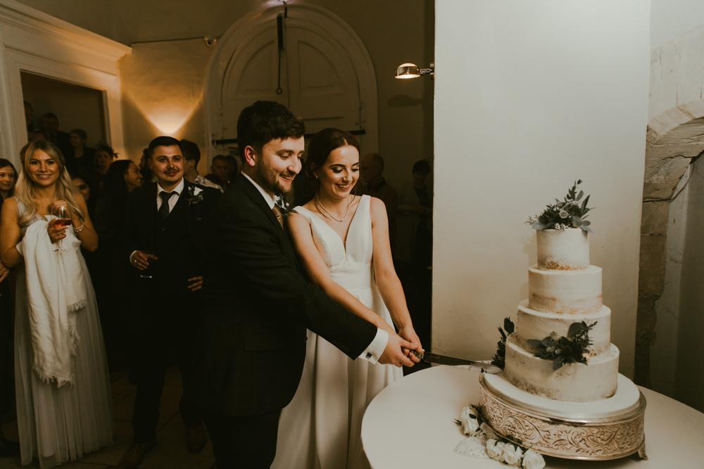 wedding cutting the cake at farnham castle bride and groom